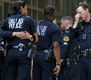 Dallas Police officers wait outside the entrance of the emergency room at Presbyterian Hospital, Tuesday, April 24, 2018, in Dallas, following a shooting at an area Home Depot where two police officers and a civilian were shot.