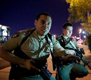 In this Oct. 1, 2017, file photo, police officers advise people to take cover near the scene of the Route 91 Harvest Music Festival mass shooting.