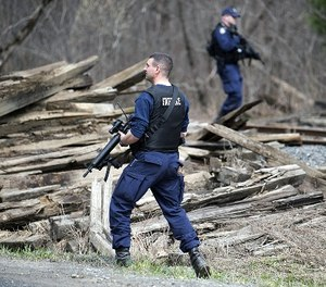 Maine state police search along railroad tracks near Mill Stream Road in Norridgewock, Maine, Friday, April 27, 2018, during a manhunt for John Williams, wanted in the shooting death of Somerset County Sheriff's Deputy Eugene Cole on Wednesday.