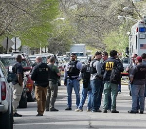 In this May 4, 2018 file photo Police from various agencies investigate the scene where a Bureau of Alcohol, Tobacco, Firearms and Explosives agent was shot, May 4, 2018, in Chicago. A law enforcement official says a suspect has been arrested in the shooting.