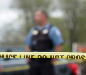 In this May 4, 2018 file photo Police from various agencies investigate the scene where a Bureau of Alcohol, Tobacco, Firearms and Explosives agent was shot, May 4, 2018, in Chicago.  (AP Photo/Teresa Crawford File)