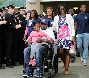 New York Police Detective Dalsh Veve, center, leaves the Kessler Institute for Rehabilitation with his wife, Esther, right, and daughter Dashi, Monday, May 7, 2018, in West Orange, N.J. Veve was critically injured in June 2017 when he was dragged by a driver in a stolen car.