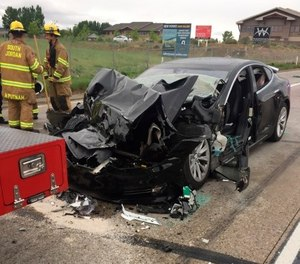 n this Friday, May 11, 2018, photo released by the South Jordan Police Department shows a traffic collision involving a Tesla Model S sedan with a Fire Department mechanic truck stopped at a red light in South Jordan, Utah. (South Jordan Police Department via AP)