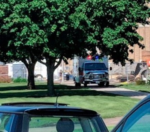 An emergency vehicle appears outside Dixon High School Wednesday, May 16, 2018 in Dixon, Ill. Officials say a police officer has shot and wounded a gunman at a northern Illinois high school.
