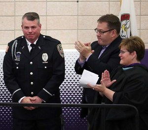 Officer Mark Dallas is honored during graduation ceremonies Sunday, May 20, 2018 at Dixon High School. (Brian Cassella/Chicago Tribune via AP)