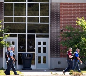 Law enforcement officers walk outside Noblesville West Middle School in Noblesville, Ind., after a shooting on Friday, May 25, 2018. (Robert Scheer/The Indianapolis Star via AP)