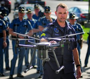In this Sept. 28, 2017, file photo, Maine State Police Sgt. Darren Foster discusses the collision avoidance system on an unmanned aerial vehicle used for traffic accident investigations, while speaking outside Maine State Police headquarters at the Central Maine Commerce Center in Augusta, Maine. (Joe Phelan/Kennebec Journal via AP, File)