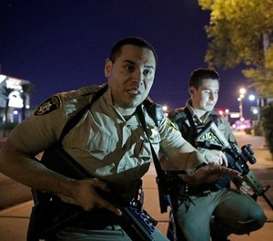 In this Oct. 1, 2017, file photo, police officers advise people to take cover near the scene of a shooting near the Mandalay Bay resort and casino on the Las Vegas Strip in Las Vegas. (AP Photo/John Locher, File)