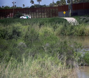 A U.S. Border Patrol vehicle sits above the Rio Grande River at the U.S. - Mexico border Tuesday, June 26, 2018, in Brownsville, Texas.