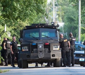 Authorities mobilize near 30th Street and Topping Avenue after three police officers were shot Sunday, July 15, 2018, in Kansas City, Mo., while trying to arrest a person of interest in the shooting death of a university student on July 6. The suspect died in an exchange of gunfire with police. (Tammy Ljungblad/The Kansas City Star via AP)