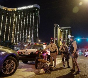 In this Oct. 1, 2017 file photo, police officers stand at the scene of a mass shooting near the Mandalay Bay resort and casino on the Las Vegas Strip, in Las Vegas. (AP Photo/John Locher, File)