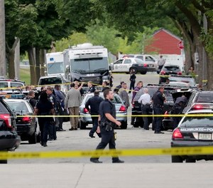 Authorities investigate the scene where a Milwaukee Police officer was fatally shot near North 28th and West Wright streets, Wednesday, July 25, 2018, in Milwaukee. A suspect is in custody.