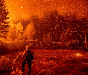 Embers fly above a firefighter as he works to control a backfire as the Delta Fire burns in the Shasta-Trinity National Forest, Calif., on Thursday, Sept. 6, 2018. (AP Photo/Noah Berger)