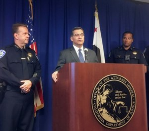 California Attorney General, Xavier Becerra, at podium, and other officials announce indictments of 32 members of purported street gangs on charges of stealing more than $1 million. (AP Photo/Don Thompson)