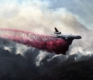 A firefighting DC-10 makes a fire retardant drop over a wildfire in the mountains near Malibu Canyon Road in Malibu, Calif. (Photo/AP)