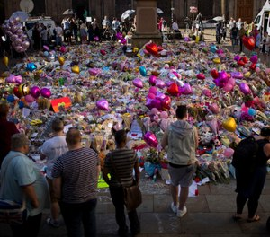 People stand near tributes placed in St. Ann's Square in Manchester, England, after a terrorist bombing in 2017 that killed 22 people attending an Ariana Grande concert. A court heard during an inquiry into the response to the bombing that only one paramedic was on the scene within the first 40 minutes after the bombing.