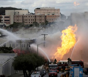 San Francisco firefighters battle a fire on Geary Boulevard in San Francisco, Wednesday, Feb. 6, 2019. The San Francisco Fire Department says several workers have been found safe after the gas explosion and fire and that no injuries have been reported. (AP Photo/Jeff Chiu)