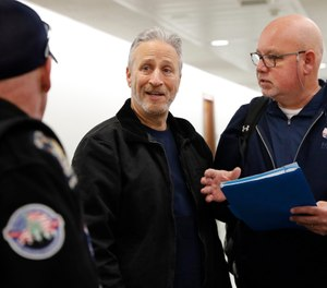 Entertainer and activist Jon Stewart, center, speaks with members of the FealGood Foundation as they arrive on Capitol Hill to speak with lawmakers about the compensation fund for victims of 9/11, Monday, Feb. 25, 2019, on Capitol Hill in Washington. (AP Photo/Jacquelyn Martin)