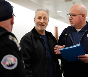 Entertainer and activist Jon Stewart, center, speaks with members of the FealGood Foundation as they arrive on Capitol Hill to speak with lawmakers about the compensation fund for victims of 9/11, Monday, Feb. 25, 2019, on Capitol Hill in Washington.
