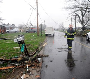 A Shelby firefighter walks down Plymouth Springmill Road just south of the intersection of Ohio Route 96, past severe storm damage to homes in Shelby, Ohio, Sunday, April 14, 2019.