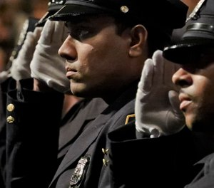 New York City Police Academy graduates salute during the national anthem at their graduation ceremony, adding 457 new members of the NYPD, Thursday April 18, 2019, in New York. (AP Photo/Bebeto Matthews)