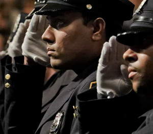 New York City Police Academy graduates salute during the national anthem at their graduation ceremony, adding 457 new members of the NYPD, Thursday April 18, 2019, in New York.