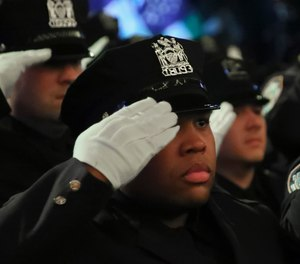 New York City Police Academy graduates salute during the national anthem at their graduation ceremony on Thursday April 18, 2019, in New York.