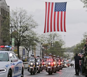 A procession escorting the body of Staff Sgt. Christopher Slutman arrives to a funeral home in the Bronx borough of New York, Monday, April 22, 2019. Firefighters in three states are honoring the U.S. Marine and New York City firefighter who was killed by a roadside bomb in Afghanistan. (AP Photo/Seth Wenig)