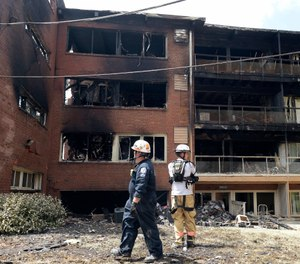 In this Aug. 11, 2016, file photo, emergency personnel view the scene of an apartment building fire in Silver Spring, Md.  (AP Photo/Susan Walsh, File)