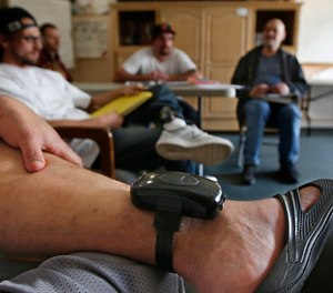 In this photo taken Wednesday, Feb. 20, 2019, a GPS bracelet is seen on the ankle of an inmate attending a discussion about living in sobriety at the Male Community Re-entry Program in Oroville, Calif.