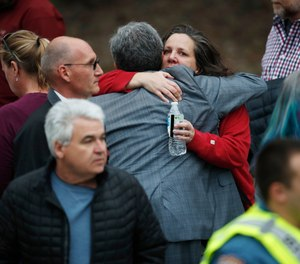 Parents hug as they wait for their children at a recreation center where students were reunited with their parents Tuesday, May 7, 2019, in Highlands Ranch, Colo. (AP Photo/David Zalubowski)