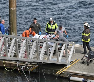Emergency response crews transport an injured passenger to an ambulance at the George Inlet Lodge docks, Monday, May 13, 2019, in Ketchikan, Alaska. The passenger was from one of two sightseeing planes reported down in George Inlet early Monday afternoon and was dropped off by a U.S. Coast Guard 45-foot response boat.