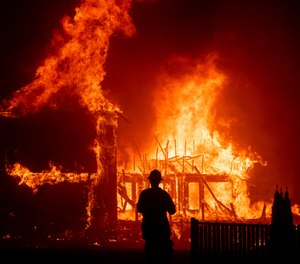 In this Nov. 8, 2018 file photo a home burns as the Camp Fire rages through Paradise, Calif. California fire authorities say that Pacific Gas and Electric equipment was responsible for the deadliest and most destructive wildfire in state history. Cal Fire said in a press release issued Wednesday, May 15, 2019, that electrical transmission lines in the Pulga area sparked the Nov. 8 fire that wiped out most of the town of Paradise and killed 85 people. (AP Photo/Noah Berger,File)