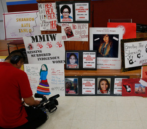 In this June 14, 2019, file photo, a photographer videos signs in memory of missing and murdered indigenous women following a march to call for justice for missing and murdered indigenous women at the Cheyenne and Arapaho Tribes of Oklahoma in Concho, Okla.