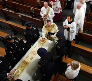 Rev. John P. Harrington blesses the casket during the funeral ceremony for Detective Luis Alvarez, at Immaculate Conception Church, in the Queens borough of New York. Alvarez, 53, who died after a three-year battle with colorectal cancer, fought until his final days for the extension of the Sept. 11 Victim Compensation Fund.