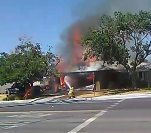 In this image taken from video provided by Ben Hood, a firefighter works to extinguish a fire following an earthquake in Ridgecrest, Calif.