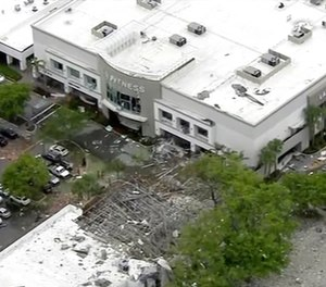This image taken from video provided by WPLG shows debris covering the parking lot of a shopping center after an explosion on in Plantation, Fla. The explosion happened Saturday morning at the shopping center, west of Fort Lauderdale in Broward County. The blast sent large pieces of debris about 100 yards (about 91 meters) across the street.