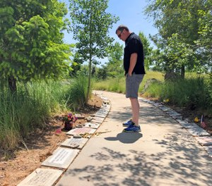 A visitor looks at memorial stones at the Wildland Firefighters Monument at the National Interagency Fire Center in Boise, Idaho.  (AP Photo/Keith Ridler)