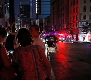 Authorities were scrambling to restore electricity to Manhattan following a power outage that knocked out Times Square's towering electronic screens and darkened marquees in the theater district and left businesses without electricity, elevators stuck and subway cars stalled. (AP Photo/Michael Owens)