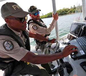 Florida Fish and Wildlife Conservation Commission officers Ronald Washington, foreground, and Guillermo Cartaya, check a computer onboard their boat as they head out to check on boaters during the first day of the spiny lobster mini-season, Wednesday, July 24, 2019, near North Miami, Fla.