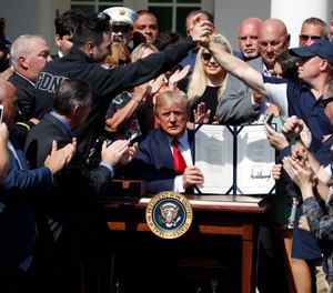 President Donald Trump holds up the signed H.R. 1327 bill, an act ensuring that a victims' compensation fund related to the Sept. 11 attacks never runs out of money, in the Rose Garden of the White House. (AP Photo/Alex Brandon)