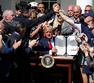 President Donald Trump holds up the signed H.R. 1327 bill, an act ensuring that a victims' compensation fund related to the Sept. 11 attacks never runs out of money, in the Rose Garden of the White House.