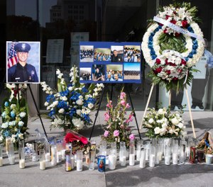 In this Wednesday, July 31, 2019 photo, a memorial for Los Angeles Police Officer Juan Diaz is on display at the Los Angeles Police Department headquarters in Los Angeles. (Sarah Reingewirtz/The Orange County Register via AP)
