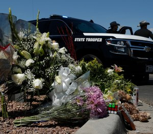 Flowers adorn a makeshift memorial near the scene of a mass shooting at a shopping complex in El Paso, Texas. (AP Photo/John Locher)