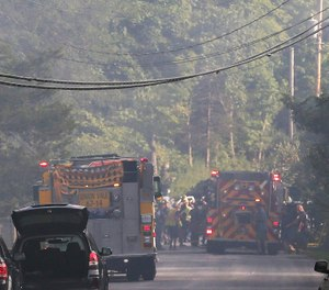 Police close off a smoke filled road as rescue workers respond to a plane that crash into a house in Union Vale, N.Y. The Federal Aviation Administration says three people were on the plane. (Photo/Frank Becerra Jr., The Journal News via AP)