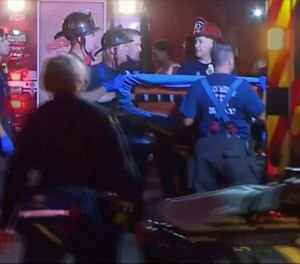 An emergency crew carries stretchers for injured persons after a light rail train was derailed in Sacramento, Calif.