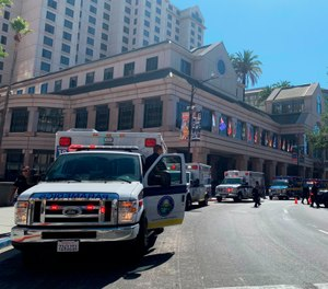 Fire crews gather on Market Street outside the Hotel Fairmont in downtown San Jose, Calif., after a report of a chemical odor. Authorities say at least one woman has died and several people have been sickened in a hazmat incident at the Northern California hotel. (Nico Savidge/San Jose Mercury News via AP)