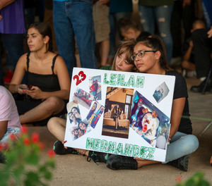 Celeste Lujan, left, and Yasmin Natera hold a sign in honor of Leilah Hernandez during a vigil for victims of the shooting spree the day before, Sunday, Sept. 1, 2019, at the University of Texas of the Permian Basin quad, in Odessa, Texas.