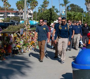 FBI agents walk past a memorial for the victims of the Conception dive boat on the Santa Barbara Harbor, as authorities issue a search warrant for the Truth Aquatics' offices in Santa Barbara, Calif.