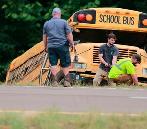 Wrecker crews work on a Benton County School bus that was involved in wreck along U.S. Highway 72 that resulted in the death of the driver and sent several students to the hospital. (Photo/Thomas Wells, The Northeast Mississippi Daily Journal via AP)